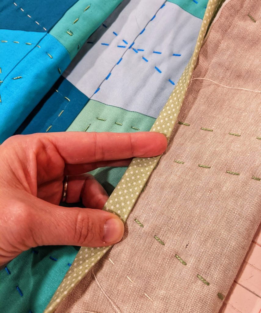Quilt binding attached to front and folded over the edge, in preparation for hand sewing