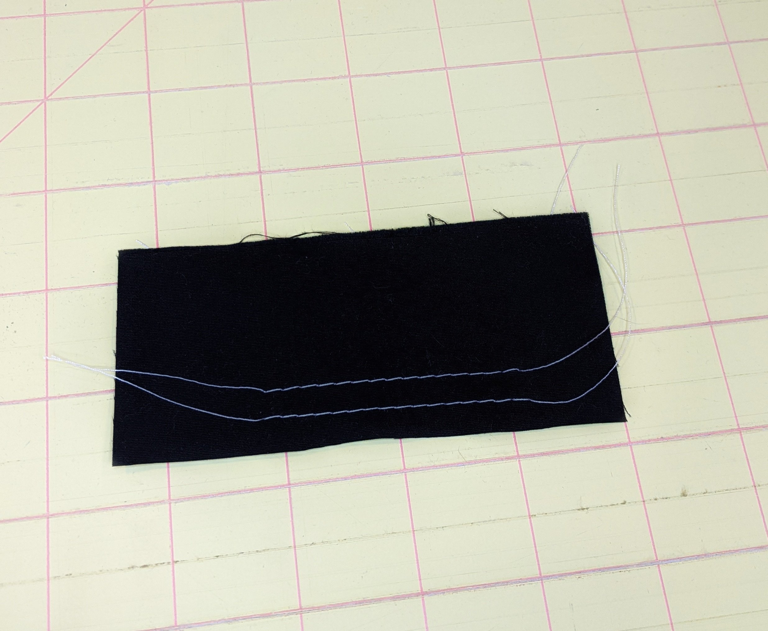 Two lines of basting stitches with long thread ends, used to gather