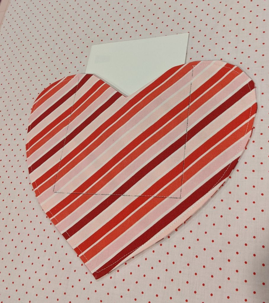 Heart pocket attached to pillow front with card inserted